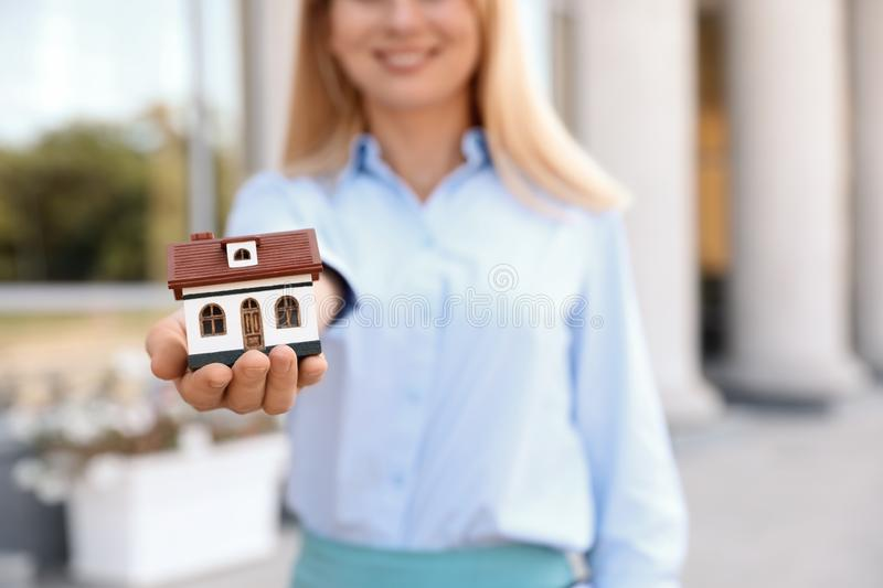 Female real estate agent with house model. Outdoors royalty free stock photos