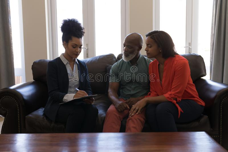 Female real estate agent and senior couple discussing over clipboard in living room stock photos