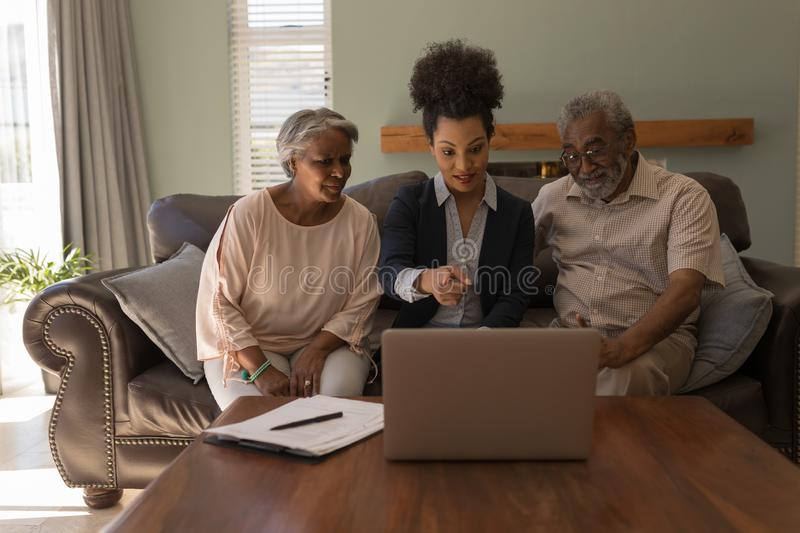 Female real estate agent and senior couple discussing over laptop. Front view of a female African American real estate agent and a senior couple discussing over royalty free stock photography