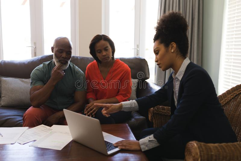 Female real estate agent and senior couple discussing over laptop. Side view of a female real estate agent and a senior couple discussing over laptop while stock image