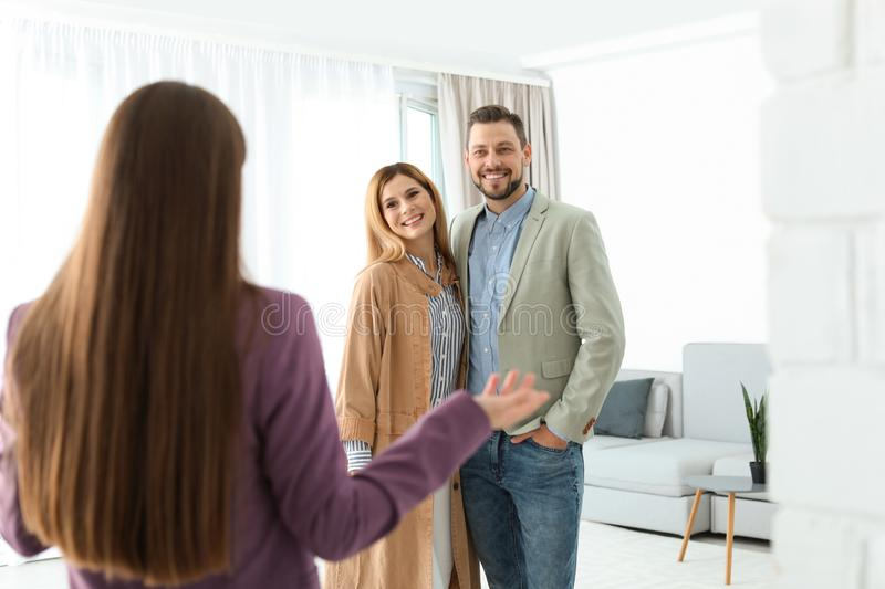 Female real estate agent showing new house to couple. Indoors royalty free stock photography