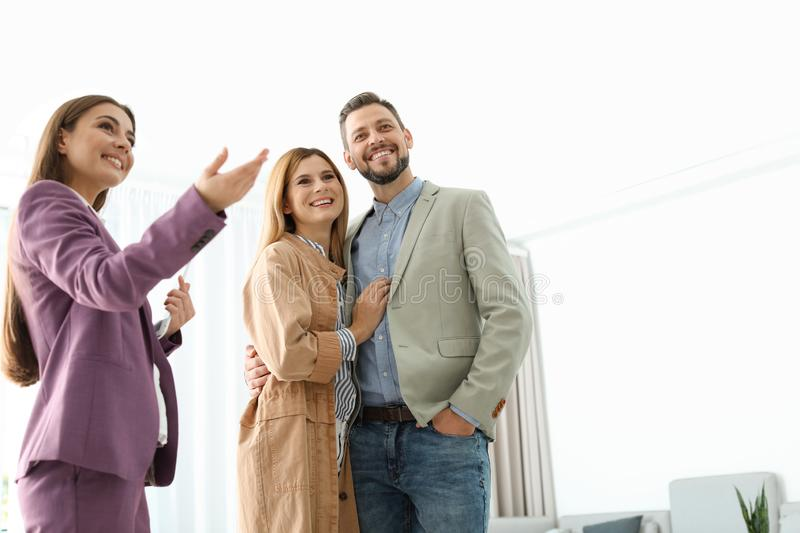 Female real estate agent showing new house to couple. Indoors stock images