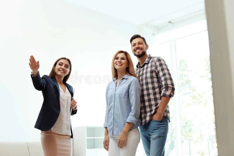 Female real estate agent showing new house to couple. Indoors stock image