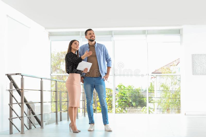 Female real estate agent showing new house to man. Indoors stock photography