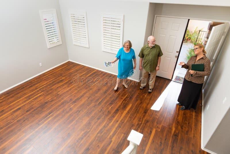 Female Real Estate Agent Showing Senior Adult Couple A New Home. Female Real Estate Agent Showing a Senior Adult Couple A New Home stock image