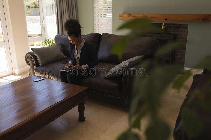 Female real estate agent using digital tablet in living room. Side view of a female African American real estate agent using digital tablet on a sofa in living stock photo