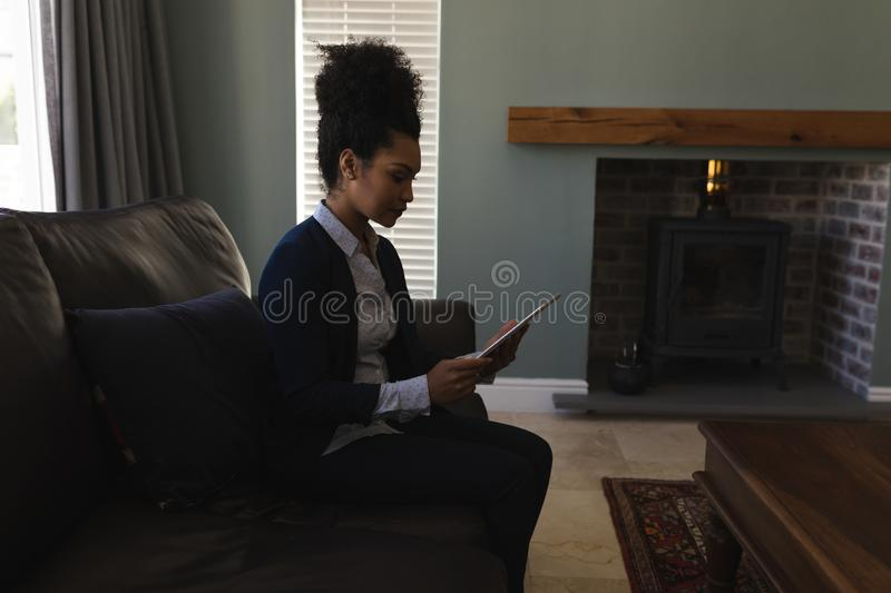 Female real estate agent using digital tablet in living room. Side view of a female real estate agent a using digital tablet while sitting on the sofa in living stock photo