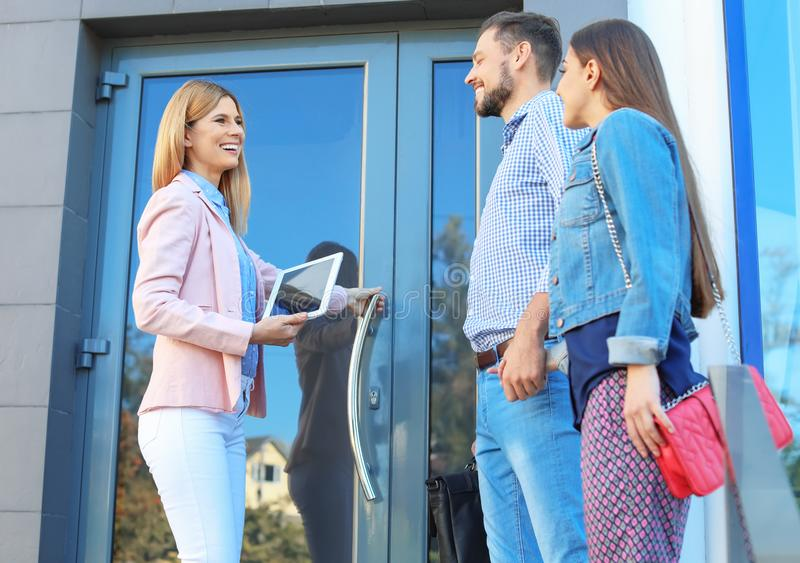 Female real estate agent welcoming couple to show hous. E, outdoors stock photo