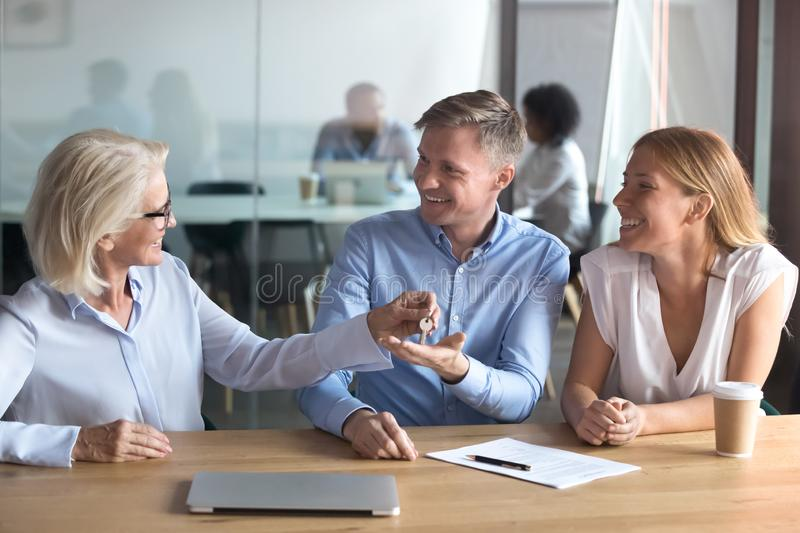 Female realtor give keys to excited married couple. Female real estate agent give keys to excited caucasian couple buying first home together, smiling husband royalty free stock photo