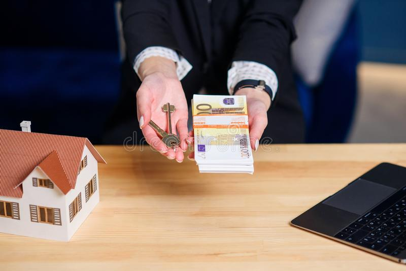 Female realtor hands with key from house and money. royalty free stock photo