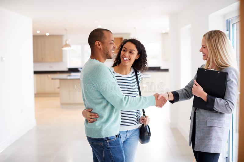Female Realtor Shaking Hands With Couple Interested In Buying House royalty free stock photography