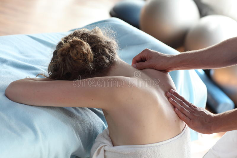 Female receiving back,shoulder massage stock images