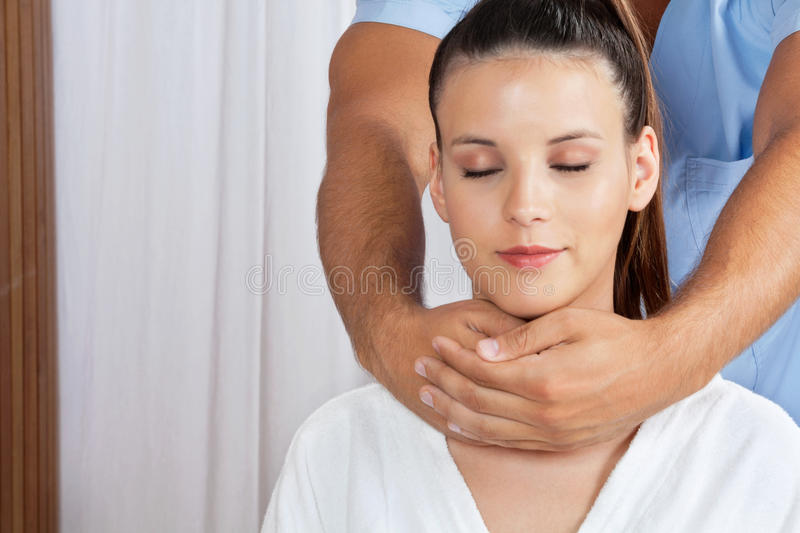 Female Receiving Neck Massage. Relaxed young female with eyes closed receiving neck massage by male masseuse royalty free stock photos