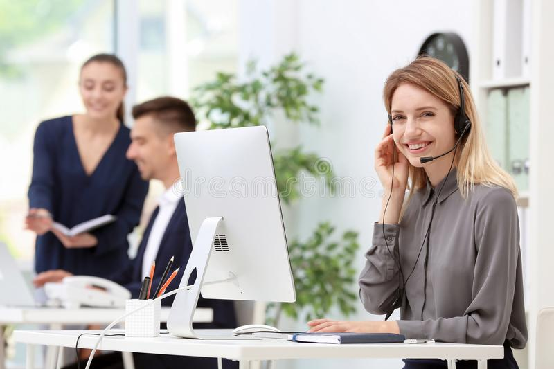 Female receptionist with headset at desk. In office royalty free stock image