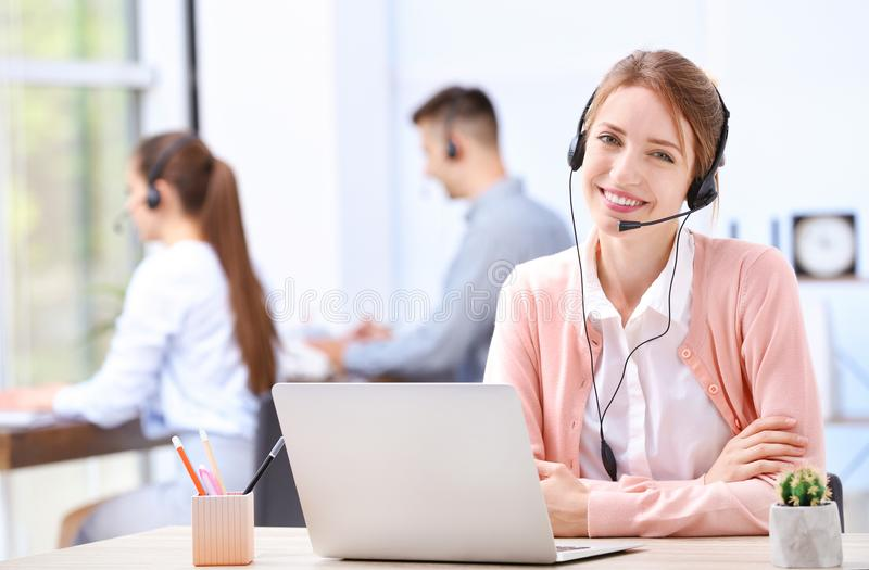 Female receptionist with headset at desk. In office stock image