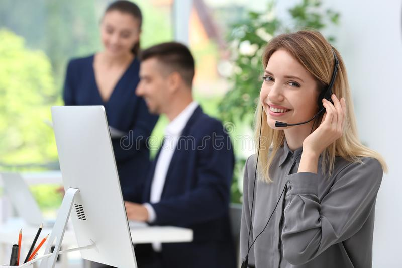 Female receptionist with headset at desk. In office royalty free stock photography
