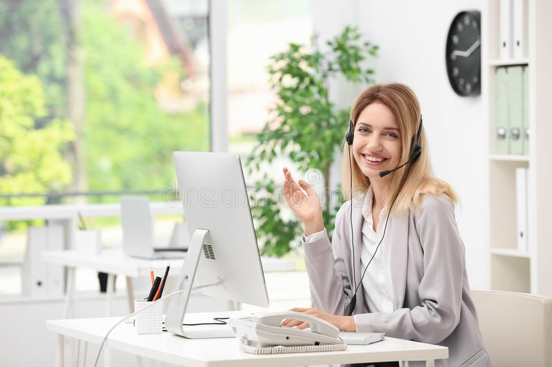 Female receptionist with headset at desk. In office royalty free stock photo