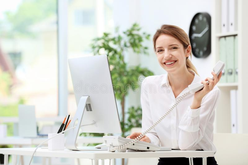 Female receptionist talking on phone at desk. In office stock image