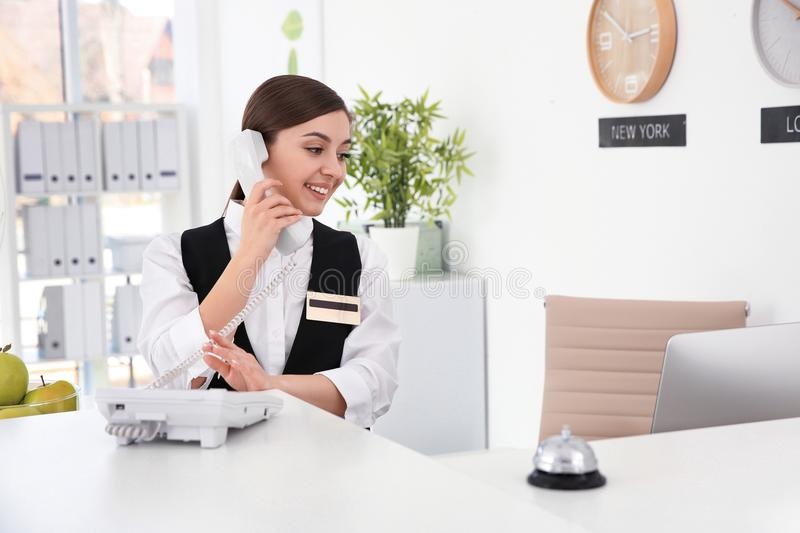 Female receptionist talking on phone at workplace royalty free stock images