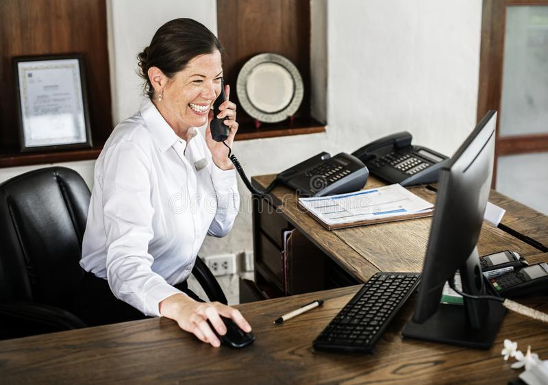 Female receptionist working at the front desk stock photo