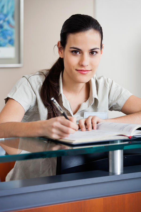 Female Receptionist Writing In Book. Portrait of pretty young female receptionist writing in book stock photos