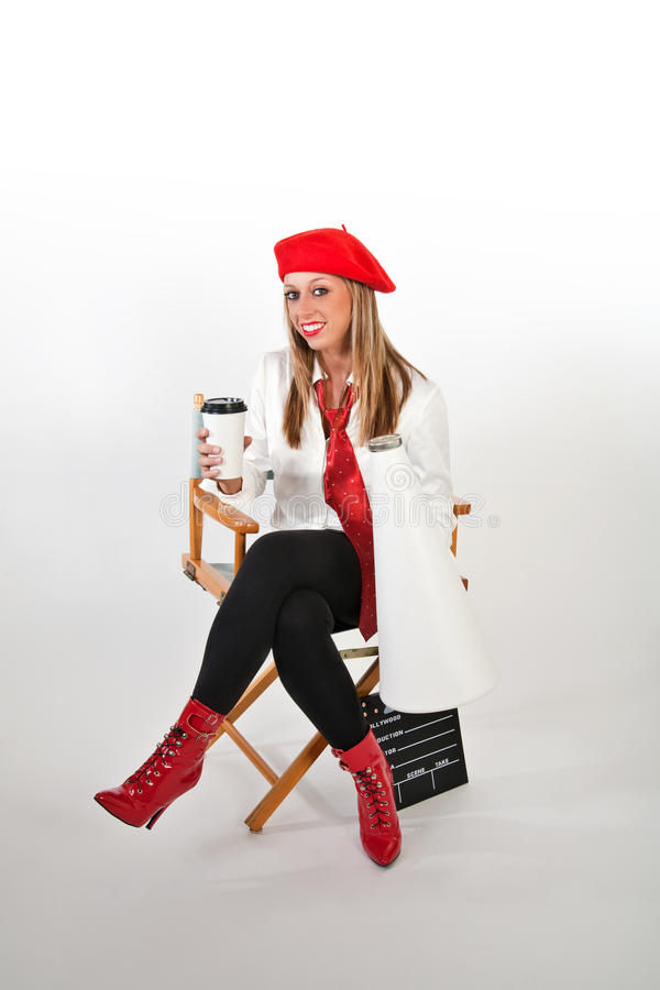 Female in Red Beret. Pretty young movie director in a red beret with a cup of coffee in one hand and a megaphone in the other royalty free stock images