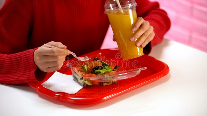 Female in red pullover drinking orange juice and eating vegetable salad in cafe stock photos