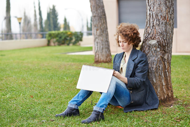 Female redhead art student drawing outdoors. At college campus stock photo