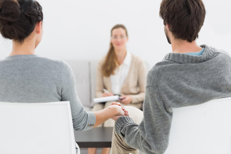 Female relationship counselor in meeting with young couple stock photos