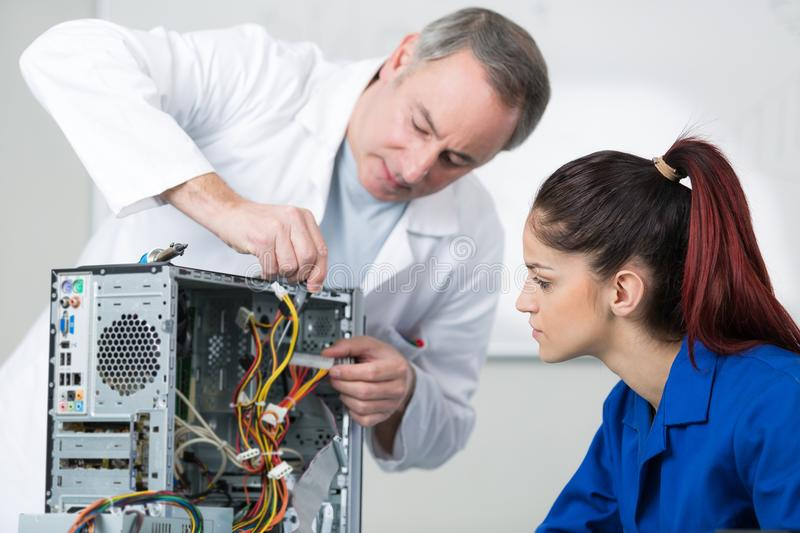 Female repairing computer in technical school. Female royalty free stock photo