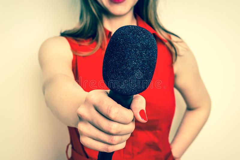 Female reporter with black microphone making interview. Journalism and broadcasting concept - retro style stock photos
