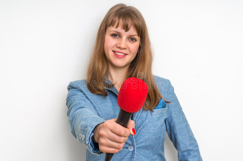 Female reporter with red microphone making interview. Journalism and broadcasting concept royalty free stock photo