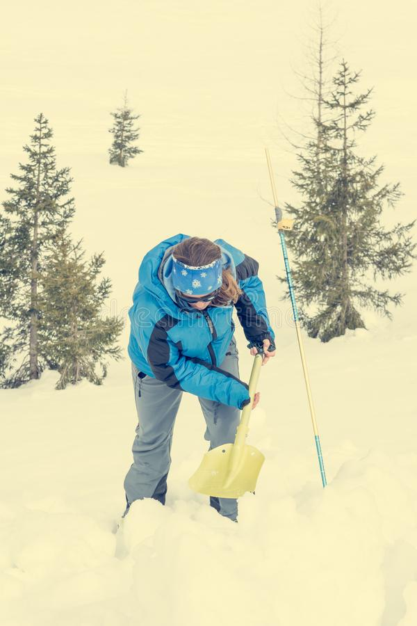 Female rescuer searching for avalanche victim. Digging for survivor stock images