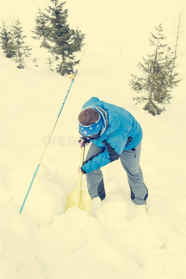 Female rescuer searching for avalanche victim. Digging for survivor royalty free stock image