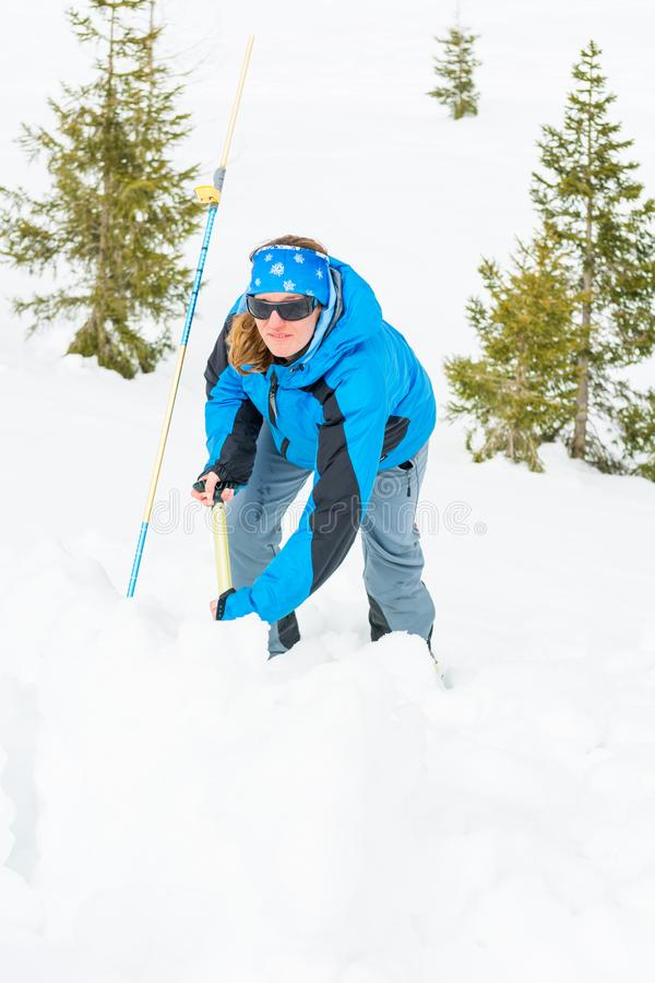 Female rescuer searching for avalanche victim. Digging for survivor royalty free stock photo