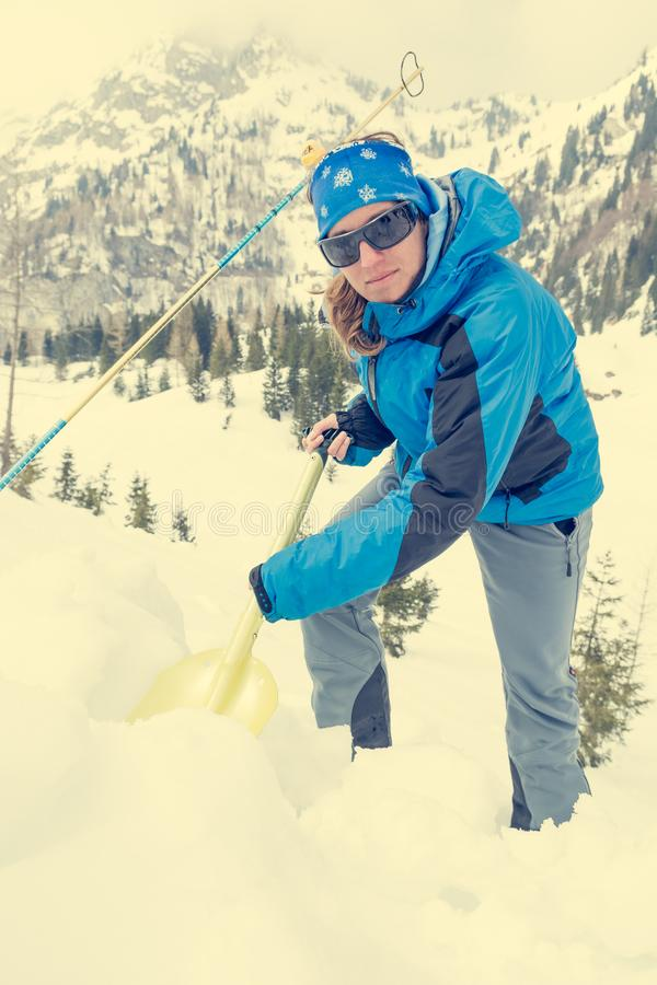 Female rescuer searching for avalanche victim. Digging for survivor royalty free stock photos