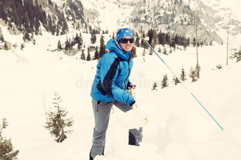 Female rescuer searching for avalanche victim. Digging for survivor royalty free stock images