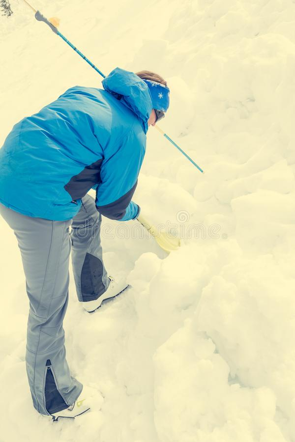 Female rescuer searching for avalanche victim. Digging for survivor royalty free stock photography