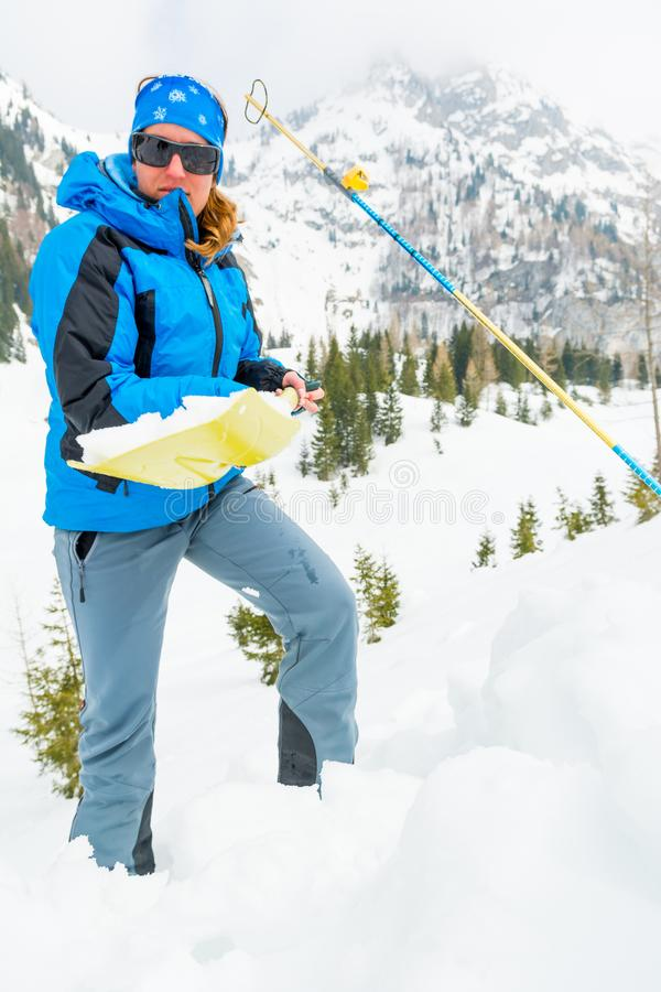 Female rescuer searching for avalanche victim. Digging for survivor stock photography