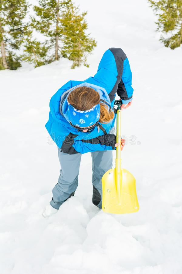 Female rescuer searching for avalanche victim. Digging for survivor stock image