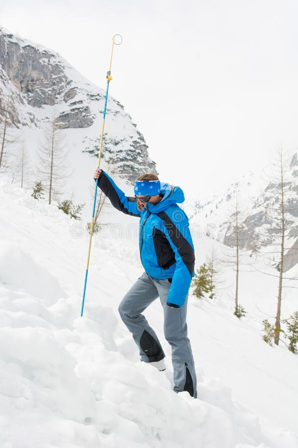 Female rescuer searching for avalanche victim. Probing for survivor stock images