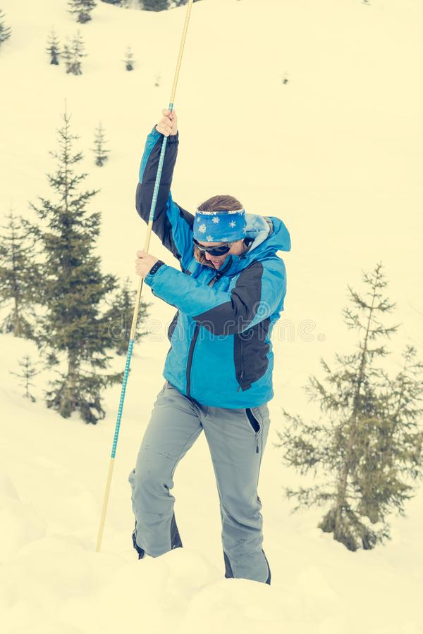 Female rescuer searching for avalanche victim. Probing for survivor royalty free stock images