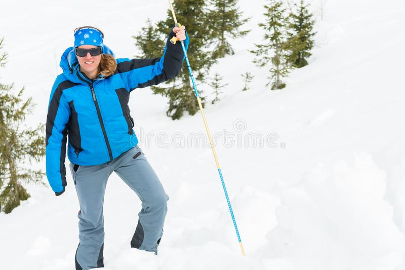 Female rescuer searching for avalanche victim. Probing for survivor royalty free stock image