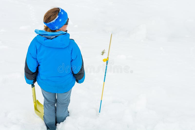 Female rescuer searching for avalanche victim. Looking for survivor royalty free stock photography