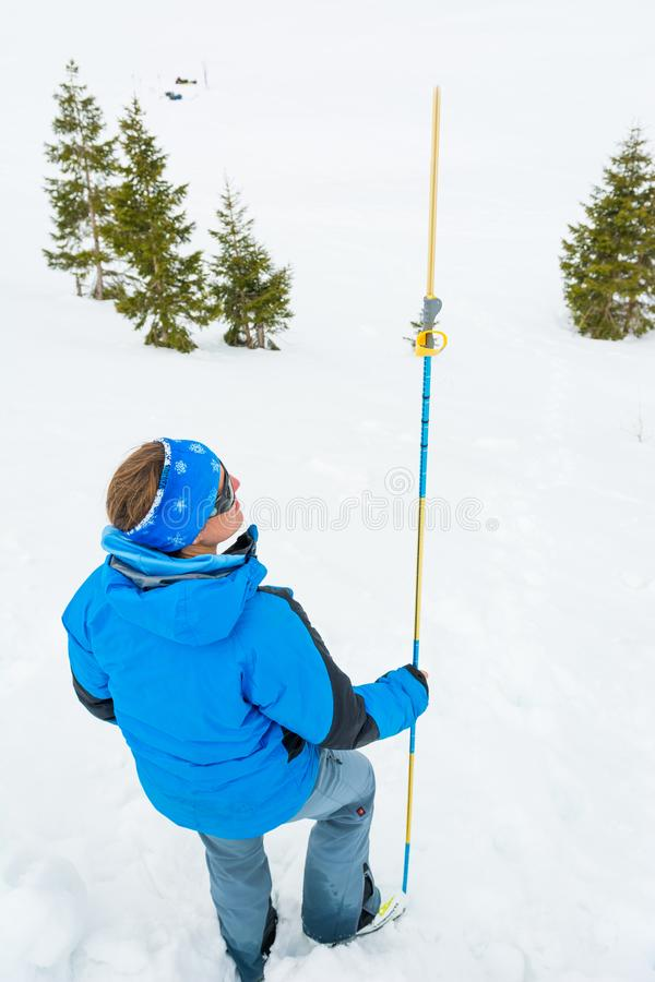 Female rescuer searching for avalanche victim. Probing for survivor stock photography
