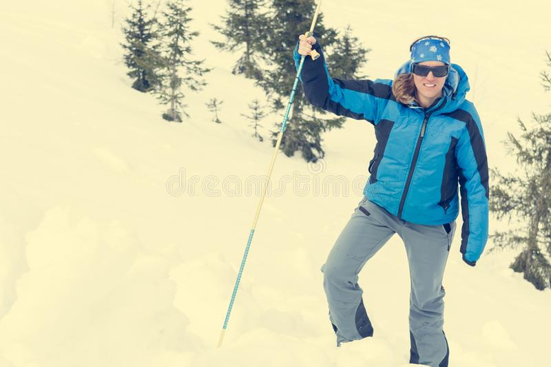 Female rescuer searching for avalanche victim. Probing for survivor royalty free stock photo