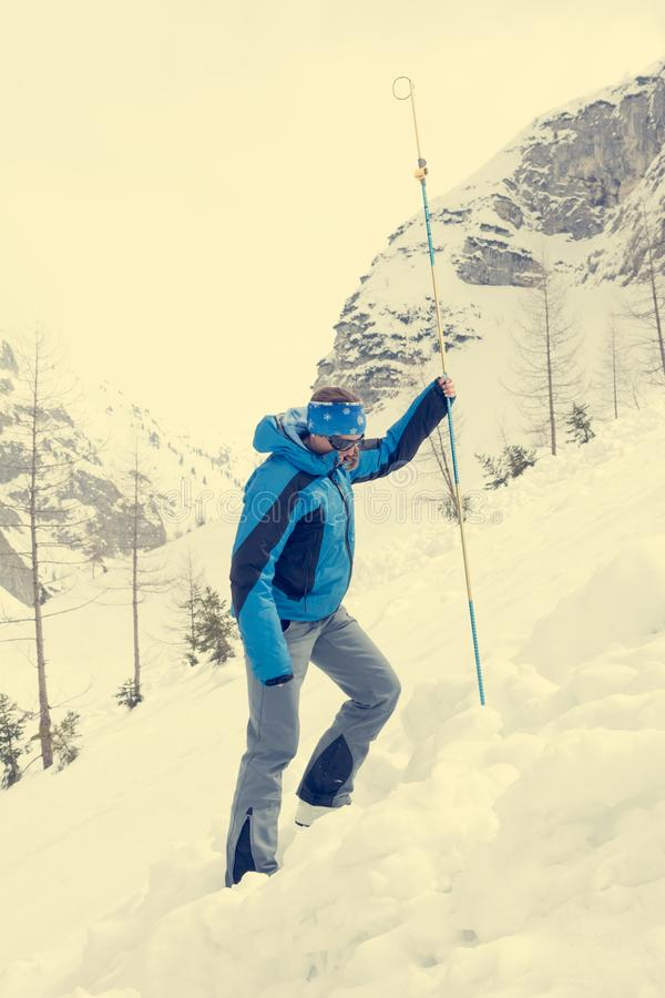 Female rescuer searching for avalanche victim. Probing for survivor stock photos