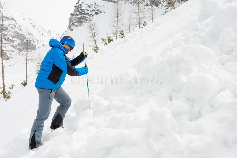Female rescuer searching for avalanche victim. Probing for survivor stock photo