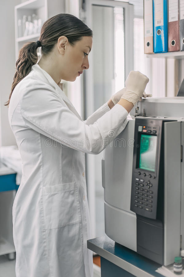 Female researcher doing research in a chemistry lab. Gas chromatograph stock image