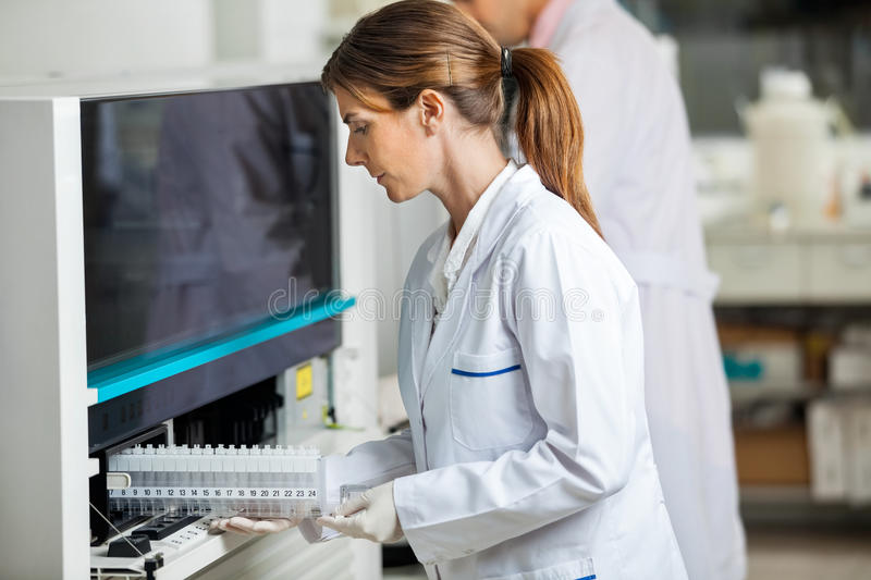 Female Researcher Loading Samples In Analyzer stock photos
